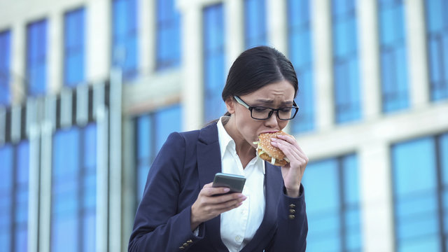 Busy business woman sending email by smartphone, biting burger, lunch break