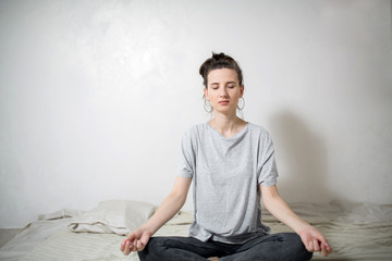 Young girl meditates in the bedroom. White background.