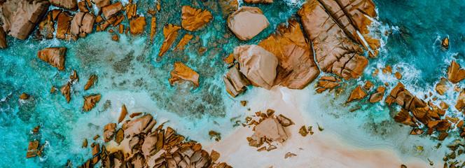 Fototapeta Aerial top panorama view of ocean shore huge bizarre granite rocks boulders on tropical beach with turquoise azure water. Amazing rock cliff seascape and coastline Seychelles La Digue Island obraz