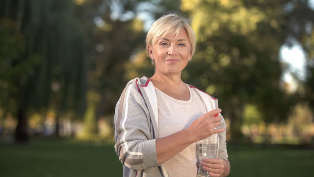 Pretty middle aged woman drinking water in park, keeping water balance, health