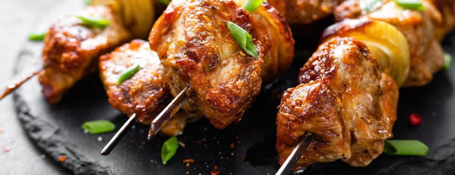 Grilled meat skewers, shish kebab on black background, banner