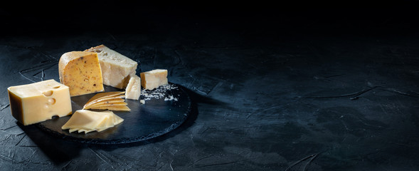 Different kinds of cheese on dark background, copy space