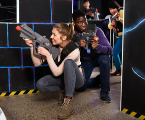 Young man and woman playing laser tag