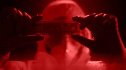 Man in lab costume watching camera roll, developing photograph in red light