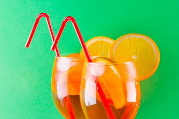 Cocktail aperol spritz on red green background. Summer alcoholic cocktail with orange slices....
