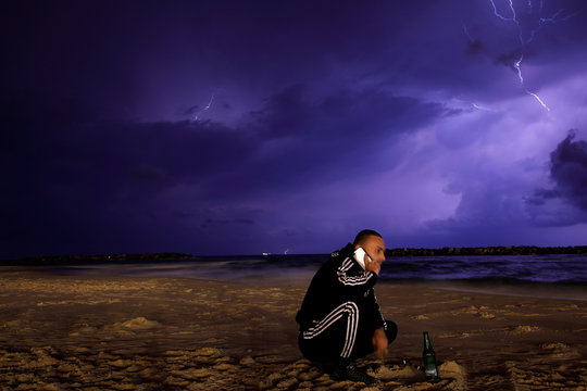 A man is seen on the beach as lightning strikes over the Mediterranean at the city of Ashkelon