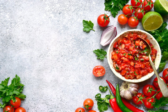 Tomato salsa (salsa roja) - traditional mexican sauce  with ingredients for making on a light grey slate,stone or concrete background.Top view with copy space.