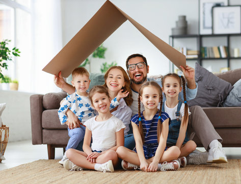 concept of housing and relocation. happy  big family mother father and kids with roof at home .