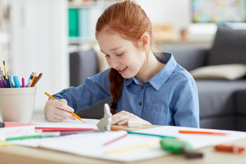 Portrait of red haired teenage girl drawing pictures sitting at table at home and smiling, copy space