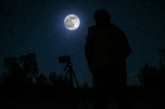 Silhouette of photographer standing with camera on tripod over Night sky with star background.