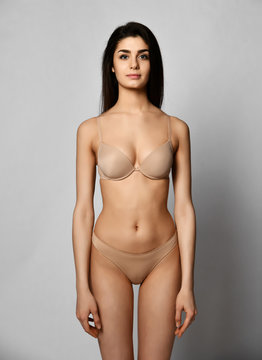 Perfect body of slim fit and sporty young woman in beige underwear on gray