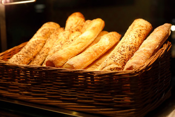 Foto op Canvas Bakkerij basket with bread sticks on bakery counter