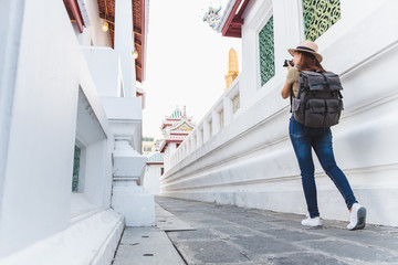Wall Mural - Asian woman travel Bangkok, Thailand, in beautiful temple during summer season, taking photo by camera