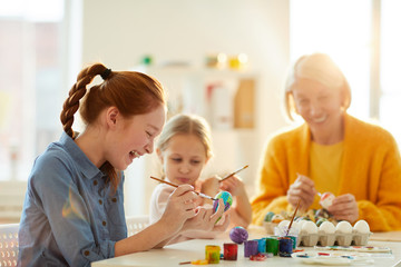 Side view portrait of excited red haired girl smiling happily while painting Easter eggs in art class, copy space