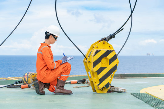 Mechanic inspector check and inspect lifting equipment of crane, he is a maintenance worker which working on offshore oil and gas wellhead remote platform.