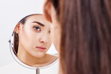 Woman with eyes bruises looks on her reflection in the mirror.