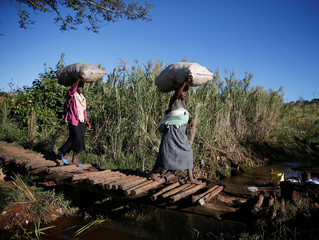 Women cross a temporary foot bridge as they carry charcoal for use as fuel, after Cyclone Idai, in Chipinge