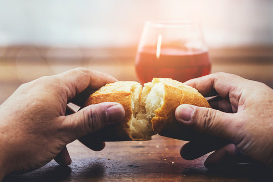 Man hand holding bread with a cup of wine  on wooden table for communion, Christian background with copy space