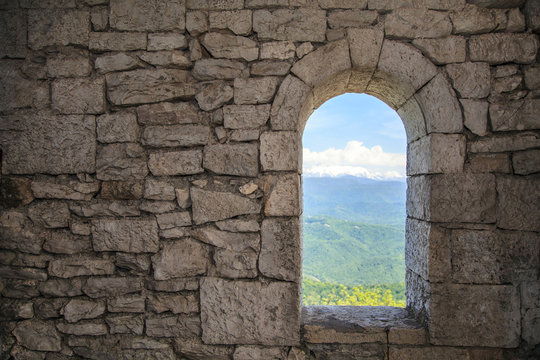 Stone war tower window with motion blurred bird and sea coast view with green tree hills