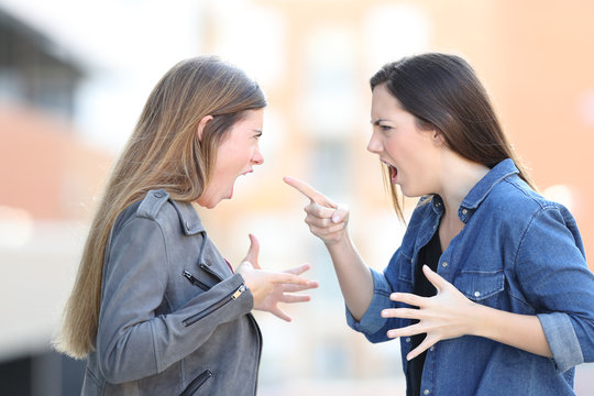 Two women fighting shouting each other in the street