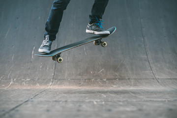 Skateboarder in action. Extreme sports lifestyle. Hipster feet performing ollie trick. Cropped shot. Copy space.