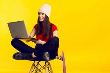 A handsome beautiful brunette girl with closed eyes, seated on a high chair, holding in hands a laptop, isolated on a yellow background, with copy space.