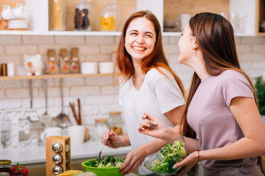 Dieting together. Female cooking fun. Two young women with salad bowls laughing loud.
