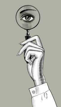Female hand holding a magnifying glass with eye inside