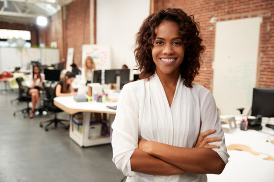 Portrait Of Businesswoman In Modern Open Plan Office With Business Team Working In Background