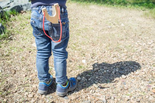 3 years little boy shooting wooden slingshot
