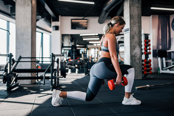 Side view of young muscular woman doing lunges in the gym.