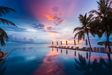 Beautiful poolside and sunset sky. Luxurious tropical beach landscape, deck chairs and loungers and...