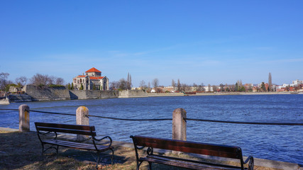 the tata castle with benches from the lake in the foreground