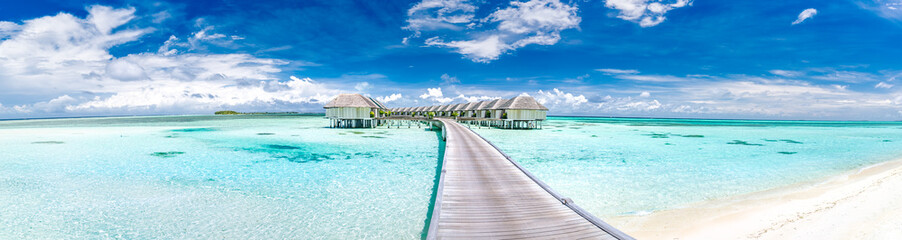 Wall Mural - Panoramic landscape of Maldives beach. Tropical panorama, luxury water villa resort with wooden pier or jetty. Luxury travel destination background for summer holiday and vacation concept.