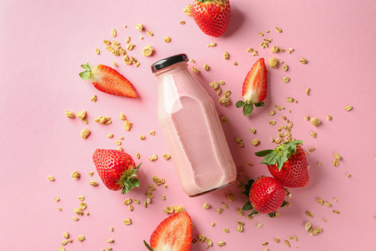 Bottle of strawberry smoothie on color background