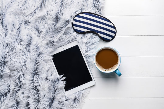 Composition with sleep mask, tablet computer and coffee on wooden background