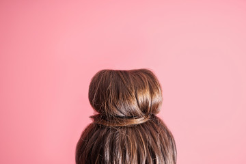 Young woman with hair bun on color background