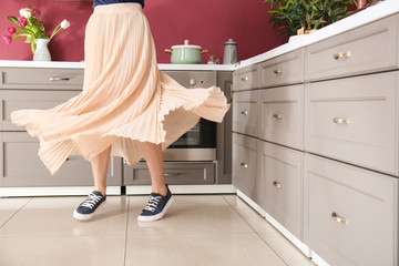 Young woman dancing in modern kitchen