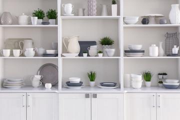 Fototapeta Open cupboard with clean dishes in kitchen obraz
