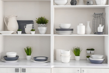 Open cupboard with clean dishes in kitchen Wall mural