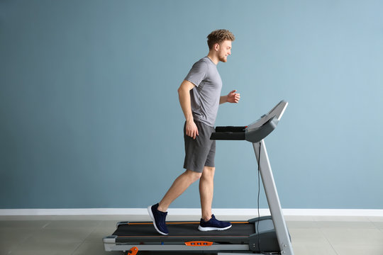 Sporty young man training on treadmill in gym