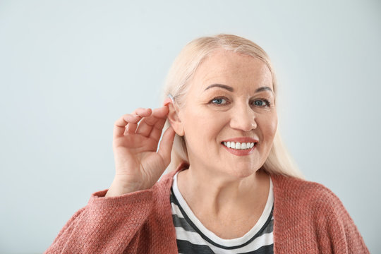 Mature woman with hearing aid on light background