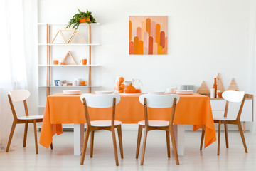 Real photo of white dining room interior with long table, four chairs, poster on the wall and wooden rack with decor and mugs