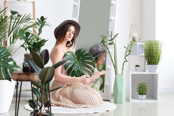 Portrait of beautiful woman with green tropical plants indoors