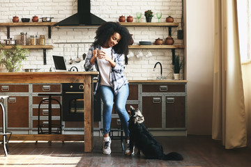 African-American woman with cute funny dog in kitchen