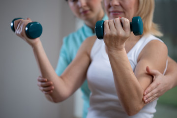 Professional physiotherapist helping senior woman to lift hand weights