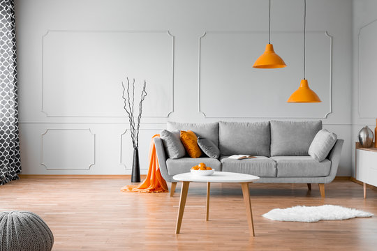 Copy space on empty grey wall of elegant orange and grey living room interior