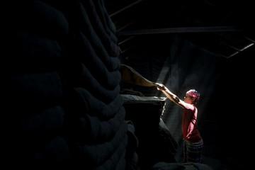 A worker stacks jute sacks in a shop in Munshiganj