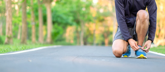 Fototapeta Young athlete man tying running shoes in the park outdoor, male runner ready for jogging on the road outside, asian Fitness walking and exercise on footpath in morning. wellness and sport concepts obraz