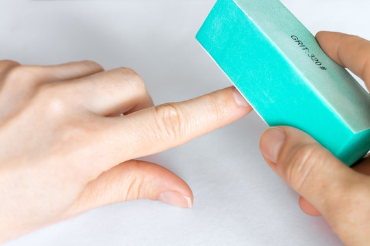 Woman buffing natural unpainted nails with buffer block.